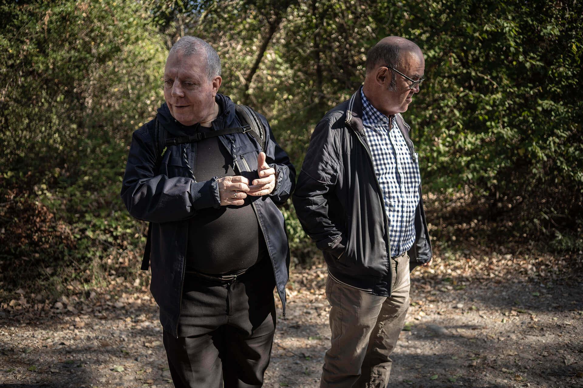 Alain et Pascal sont devant un bosquet. Chacun regarde dans une direction opposée.
