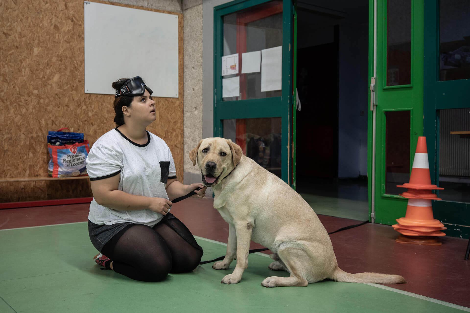 Meryem, jeune-femme non-voyante, est assise face à Mystère, son chien guide. Son visage est tendu vers le haut tandis que Mystère regarde à droite de la photo. Derrière eux, l'entrée du gymnase.