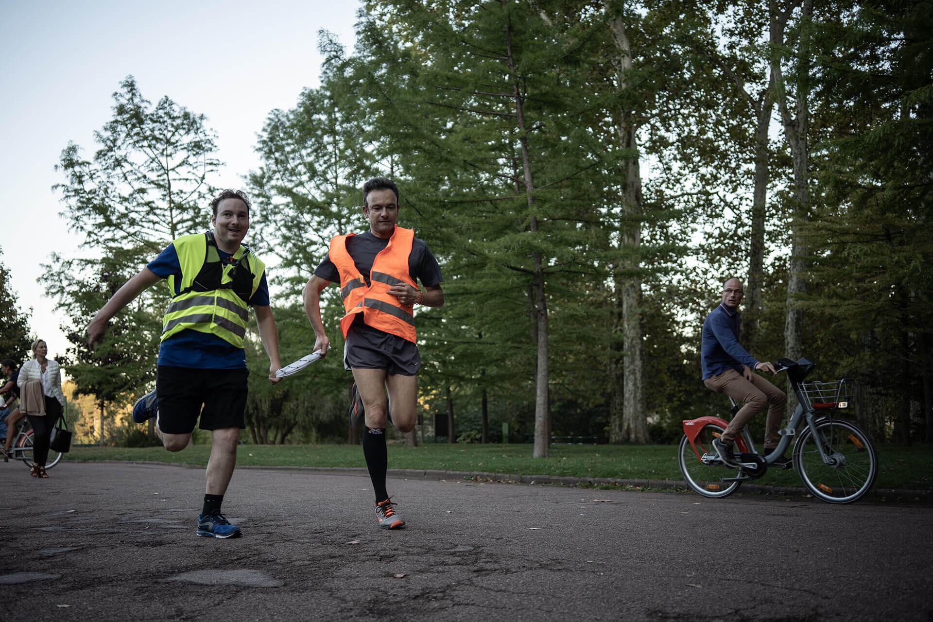 Jocelyn court avec Jean-Michel dans l'une des allées du parc de la Tête d'Or. Un bandeau les relie. Sur la gauche de la photo, on peut voir une femme qui rentre probablement du travail tandis qu'un homme à vélo regarde les coureurs, sur la droite.
