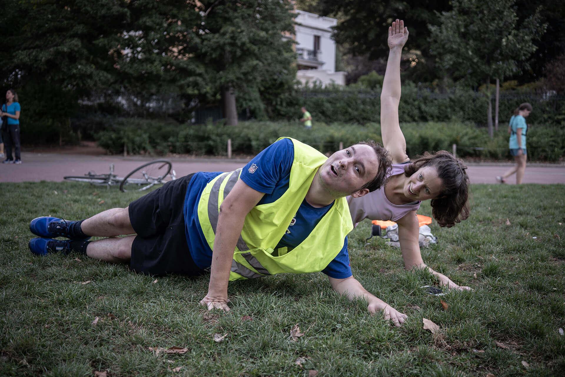 Jocelyn et Sarah sont allongés sur l'herbe, en train de faire du gainage. Sarah, derrière lui et à sa droite, lève le bras droit vers le ciel tandis que Jocelyn maintient le haut du corps tendu appuyé sur ses deux bras.