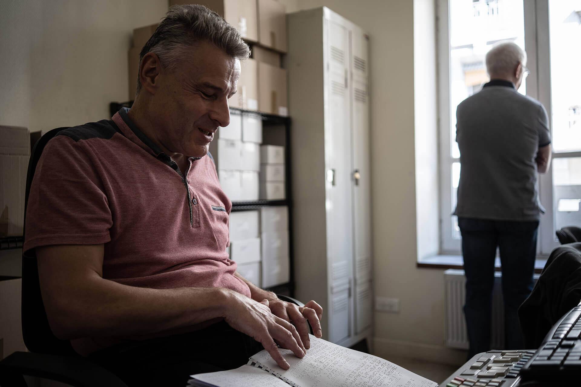 Jean-François est assis devant une table avec, sur les genoux, une épreuve du National Geographic en braille. Dans le fond de l'image, un homme de dos regarde par la fenêtre.