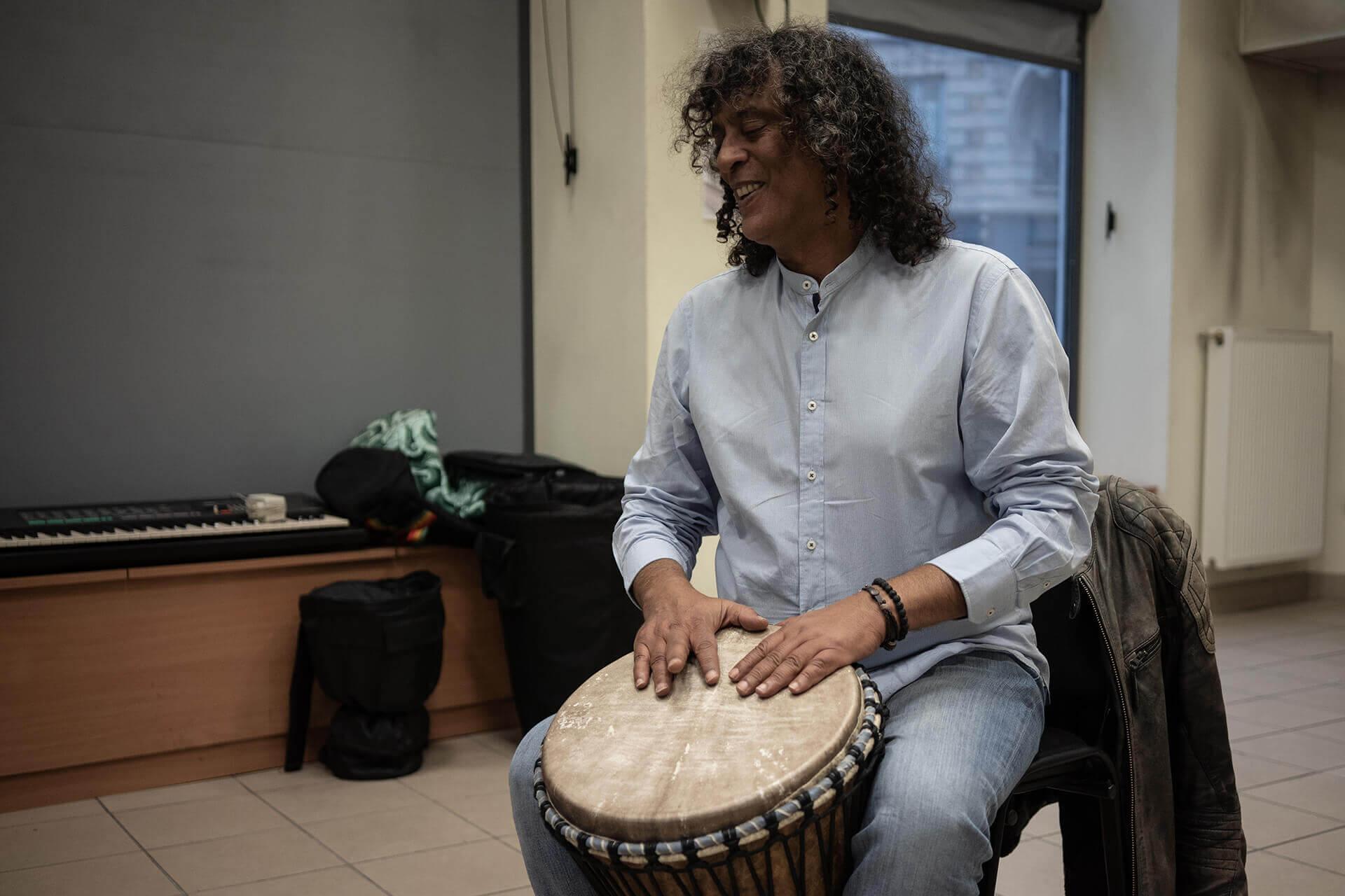 Khaled, professeur de djembé non-voyant, est assis sur une chaise en train de jouer de son instrument. Il sourit, la tête légèrement inclinée vers sa droite. Derrière lui, un piano électrique repose dans un coin de la salle.