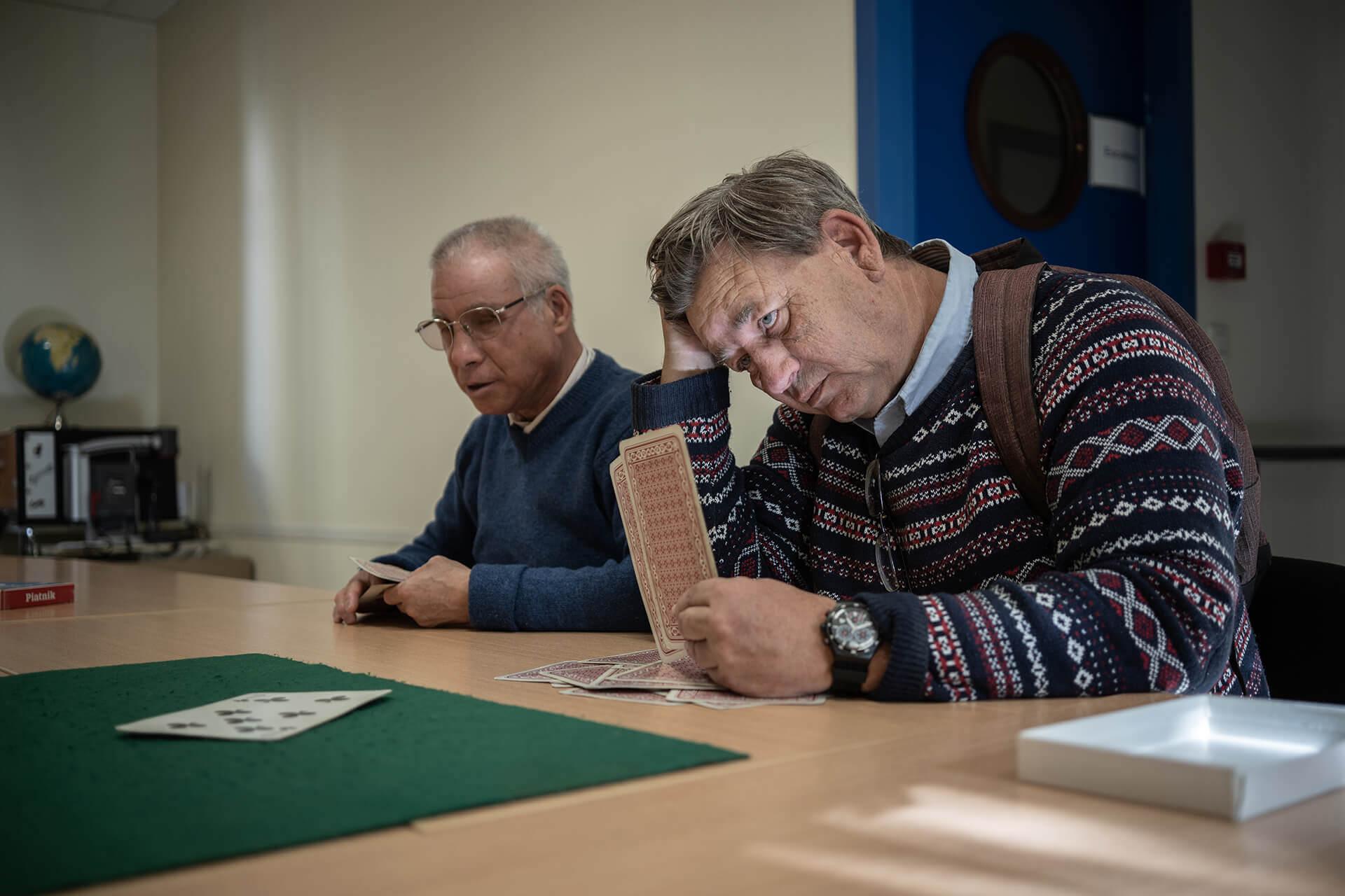 Dans une salle de l'association Valentin Haüy, à Lyon, Jean-Marie, non-voyant, assis à gauche sur la photo, joue à la belote avec Patrick, à droite. Tous deux tiennent des cartes en main. Un tapis de jeu vert leur fait face sur la table. Patrick, coude posé, se tient la tête.
