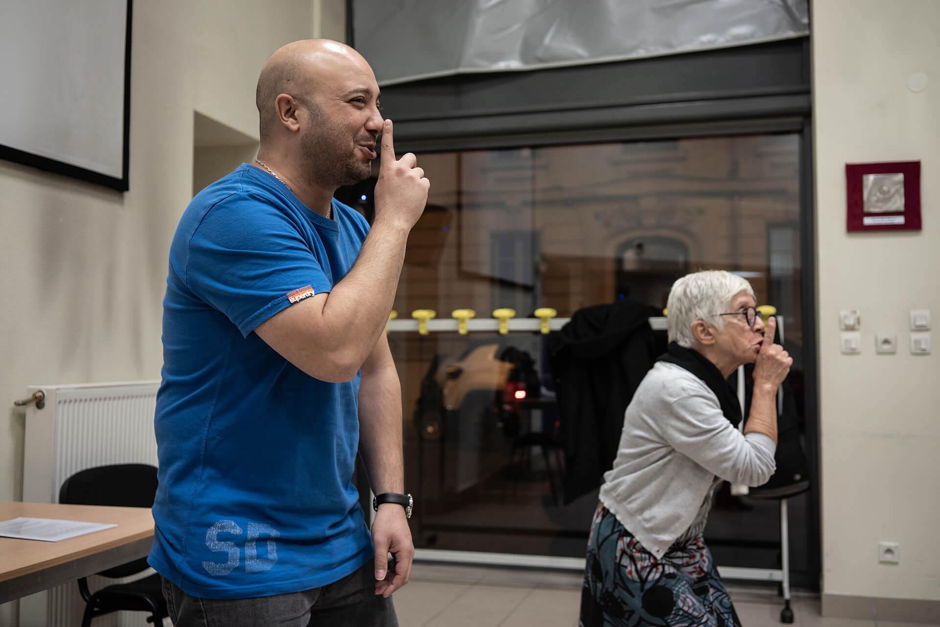 Cours de théâtre dans une des salles de l'association Valentin Haüy, à Lyon. A la demande de Jérôme (le professeur), Nabil, malvoyant, à gauche sur la photo, et Martine font le signe, doigt sur la bouche, que l'on réalise parfois pour demander le silence. Nabil sourit de l'exercice tandis que Martine affiche un peu plus de sérieux.