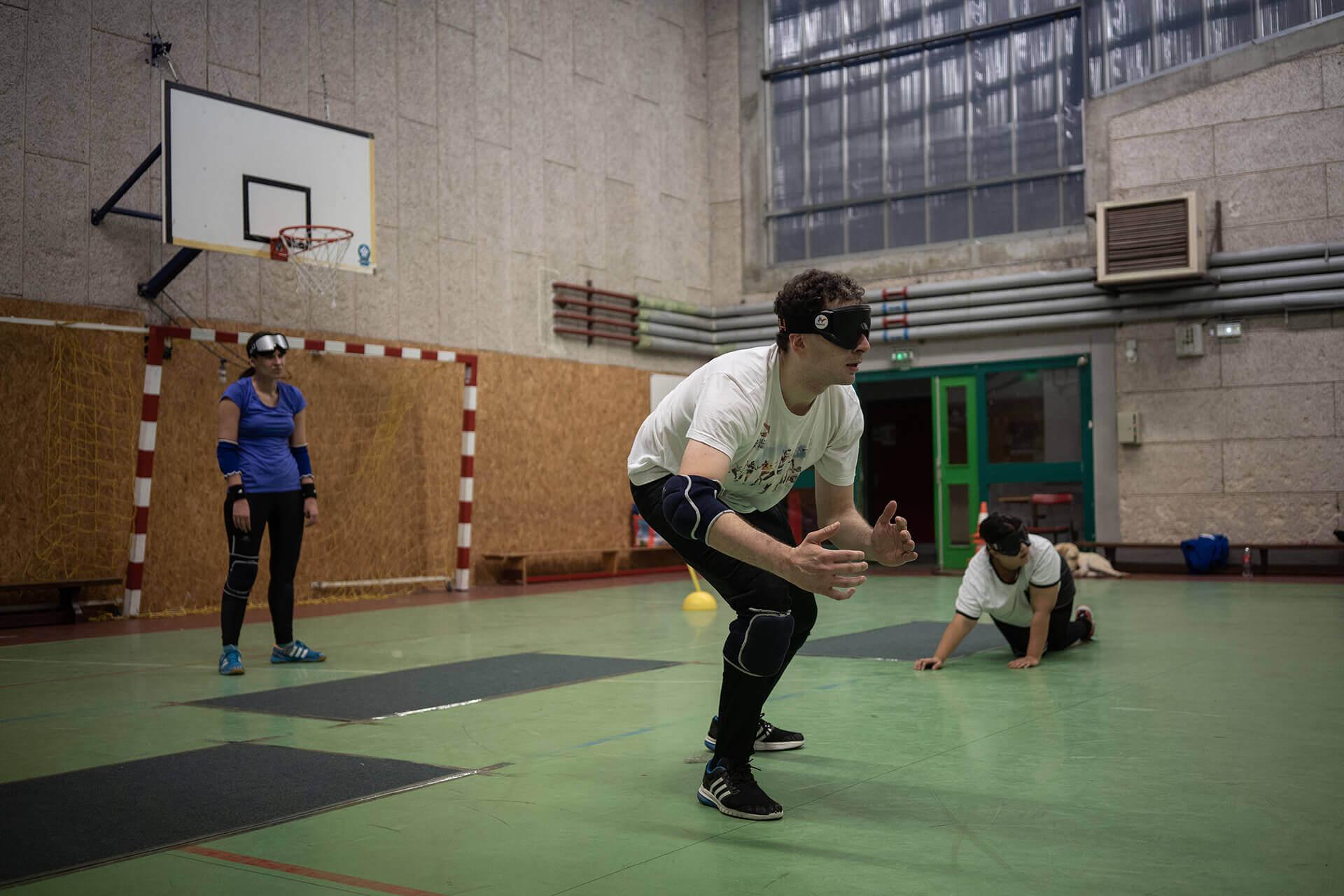 Dans un gymnase de Villeurbanne : à gauche de la photo, Nadège, puis Haris au centre et enfin Meryem, à droite. Ils jouent au torball. Haris, jambes fléchies et bras pliés, attend la balle qui doit arriver face à lui.