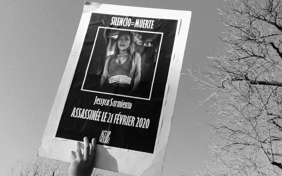 Photographie d'une main levée tenant une pancarte en hommage à Jessyca Sarmiento, portant le slogan Silencio = Muerte